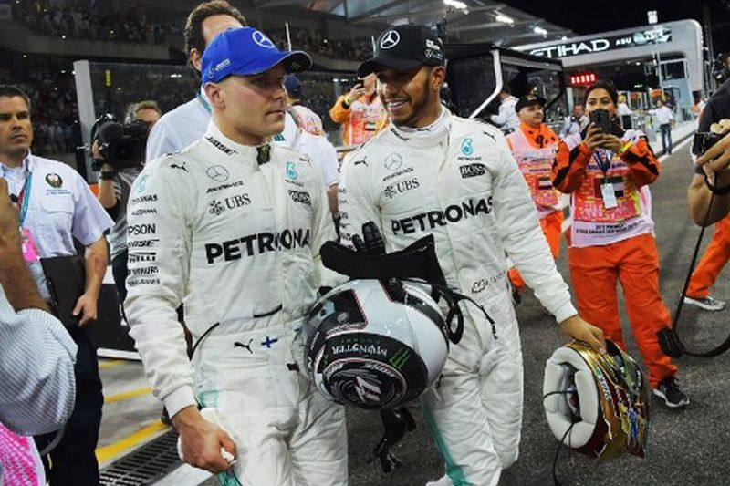 Mercedes' Finnish driver Valtteri Bottas (L) celebrates with his teammate British driver Lewis Hamilton after taking the pole position at the end of the qualifying session ahead of the Abu Dhabi Formula One Grand Prix at the Yas Marina circuit on November 25, 2017. Valtteri Bottas outpaced his Mercedes team-mate Lewis Hamilton to claim pole position with a record-breaking lap in the qualifying session for Sunday's season-ending Abu Dhabi Grand Prix. German four-time champion Sebastian Vettel took third place for Ferrari ahead of Australian Daniel Ricciardo of Red Bull and his Ferrari team-mate Kimi Raikkonen, with Dutchman Max Verstappen sixth in the second Red Bull. / AFP PHOTO / GIUSEPPE CACACE