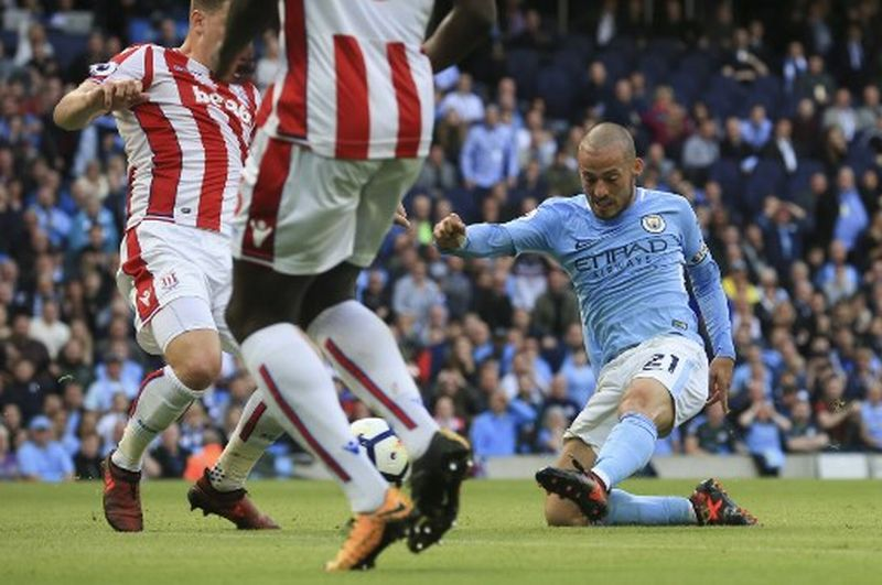 Manchester City's Spanish midfielder David Silva scores their third goal during the English Premier League football match between Manchester City and Stoke City at the Etihad Stadium in Manchester, north west England, on October 14, 2017. / AFP PHOTO / Lindsey PARNABY / RESTRICTED TO EDITORIAL USE. No use with unauthorized audio, video, data, fixture lists, club/league logos or 'live' services. Online in-match use limited to 75 images, no video emulation. No use in betting, games or single club/league/player publications.  /